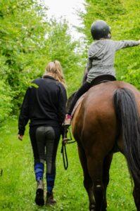 pige sidder på hest, kvinde holder hesten