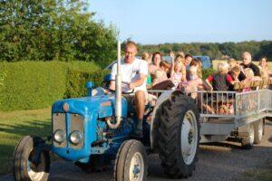 mand kører traktor med en trailer med nogle personer i