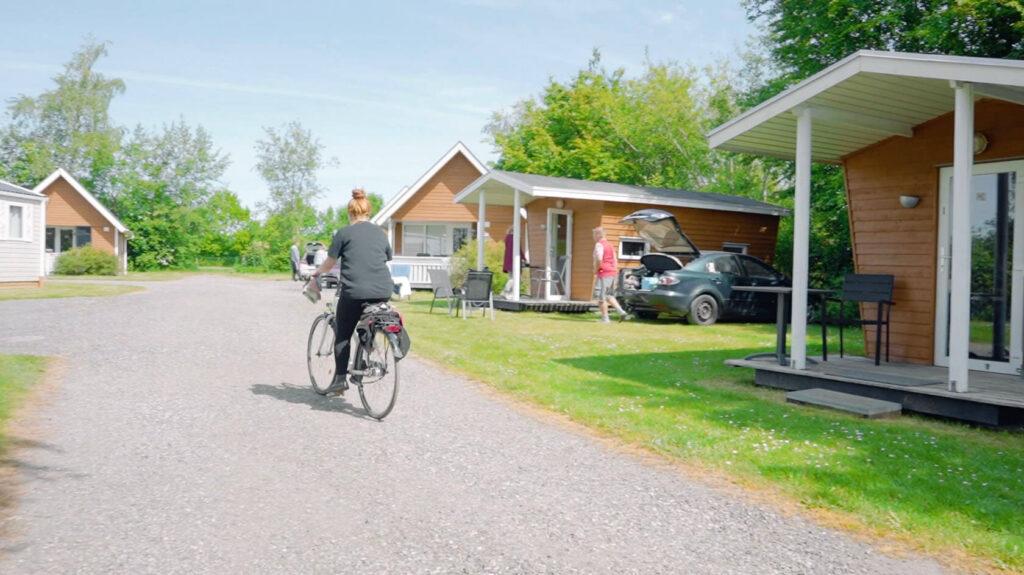 Kvinde cykler forbi nogle hytter, person går ved siden af bil med åbent bagerum